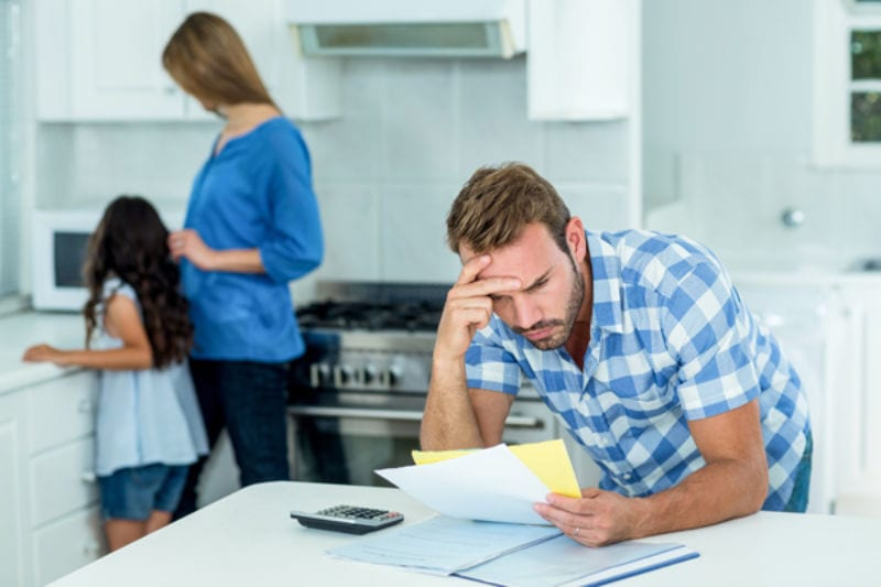 Worried father looking at bills at home