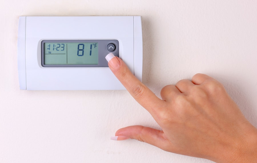 thermostat. woman's hand setting the room temperature on a modern programmable wall heater. closeup, How to Set Your Programmable Thermostat